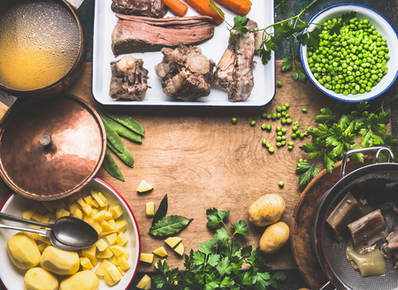 Potatoes soup with green pea and meat, cooking preparation on rustic kitchen table, top view, frame