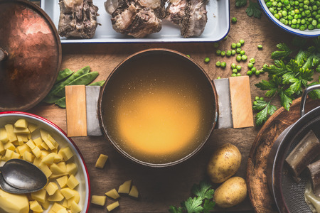 Pot with meat broth , cooking preparation for potatoes soup with green peas, top view