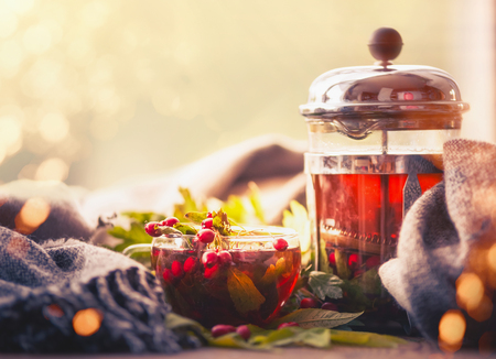Autumn still life with cup and tea pot with berries, scarf  and fall leaves at sunny bokeh background Stock Photo