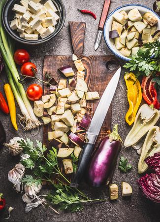 ナイフで木製のまな板にみじん切りナスと様々 な菜食主義者の健康的な食生活のための食材を調理平面図です。バルカン料理コンセプト