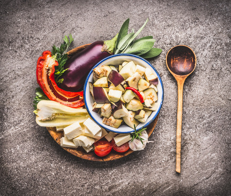 Healthy vegetarian cooking ingredients for Balkan cuisine: vegetables, eggplant, paprika, herbs and spices , balkan cheese with cooking spoon, top view