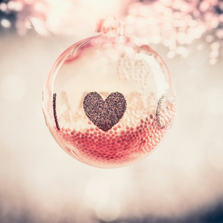 Red glass Christmas hanging ball with heart at bokeh background, festive greeting card