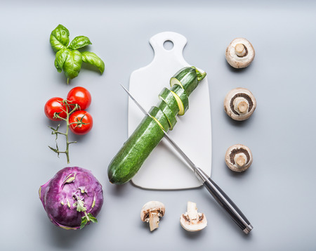 Healthy vegetarian clean food concept with vegetables cooking ingredients:  cutting board and knife on gray background, top view, flat lay