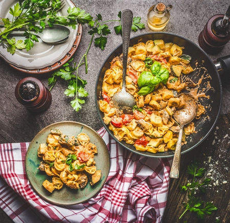 Tasty tortellini pot with vegetables sauce served on plate with spoons and greens on rustic kitchen table background, top view. Healthy vegetarian cooking and eating. Italian food concept Stock Photo