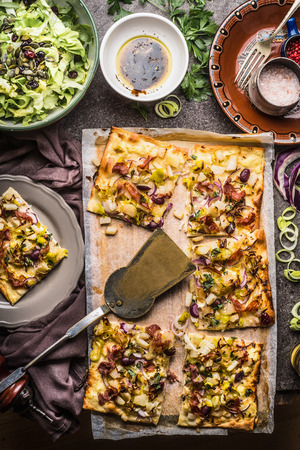 Tarte flambee or open vegetable pie with vegetables and salad on rustic kitchen table background with plates and tools, top view. Seasonal German food