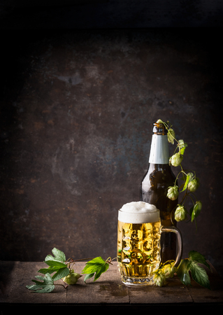 Glass bottles and mug of beer with cap of foam and hops on table at dark rustic background, front view, Still life