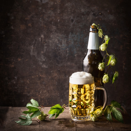 Glass bottles and mug of beer with cap of foam and hops on table at dark rustic background, front view, Still life , close up