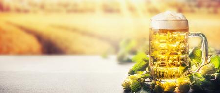 Mok bier met schuim op tafel met hop op de achtergrond van de gebiedsaard met zonnestraal, vooraanzicht, banner