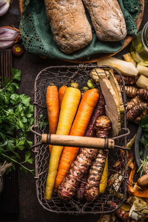 Colorful root vegetables in harvest basket on dark wooden kitchen table background, top view. Healthy and clean food and eating  concept.