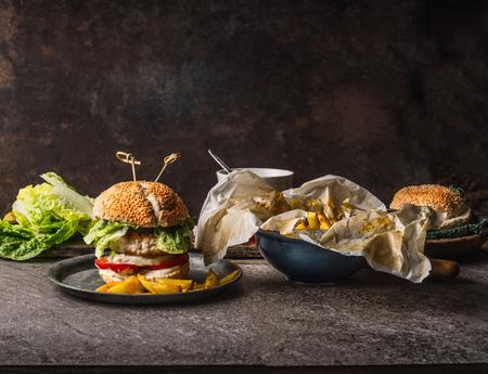 Burger savoureux faits maison avec du poulet, laitue, mozzarella et tomates servis avec des pommes de terre frites sur fond de table de cuisine rustique avec des ingrédients, vue de face Banque d'images - 88129588