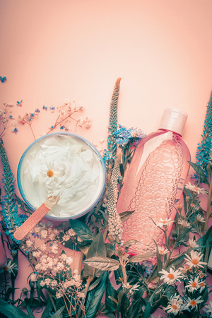 Herbal dermatology cosmetic cream and lotion with flowers . Skincare products on pastel background, top view