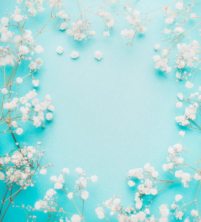 Beautiful white little flowers on light blue turquoise background, top view, frame. Stock Photo