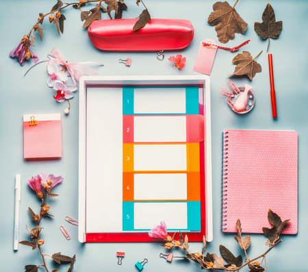 Modern female home office desktop in pink red color with flowers , accessories and planner wallet on blue background,top view. Flat lay, mock up. Stock Photo