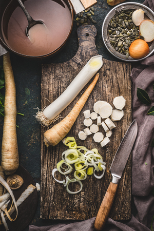 Healthy vegetables cooking and eating concept. Leek and parsnip root vegetables on cutting board with knife and pot with bread on dark rustic background, top view. Zdjęcie Seryjne