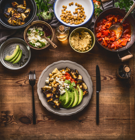 Healthy vegetarian meal. Bowl with chick peas puree, roasted vegetables , red paprika tomatoes stew, avocado and seeds . Clean eating or dieting food concept