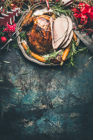 Christmas ham served with roasted vegetables and festive decorations on vintage background, top view, place for text, vertical. Christmas recipes and dishes concept Stockfoto