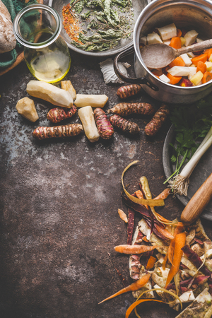 Cooking preparation of organic colorful farm root vegetables : Jerusalem artichoke, carrot, celery,parsnip on rustic kitchen table background, top view, place for text. Healthy food and eating concept