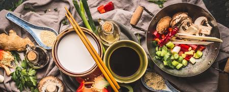 채식 볶음 재료 : 다진 야채, 향신료, 코코넛 밀크, 간장, 냄비와 젓가락, 상위 뷰, 배너. 아시아 음식, 중국 또는 태국 요리 컨셉