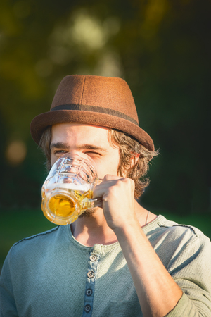 Happy young man drinking beer from the cup