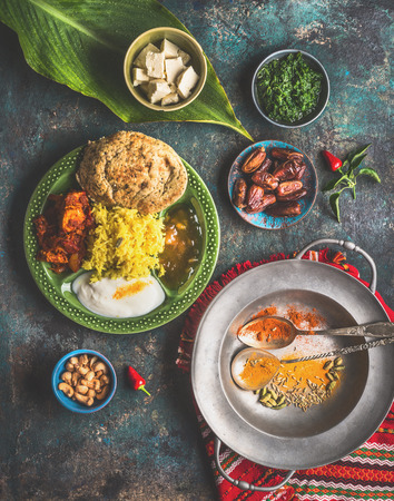 Indian food meals in bowls served with banana leaf: Curry, butter chicken, rice, lentils, paneer, samosa, naan, chutney, spices.  Traditional south indian cuisine.