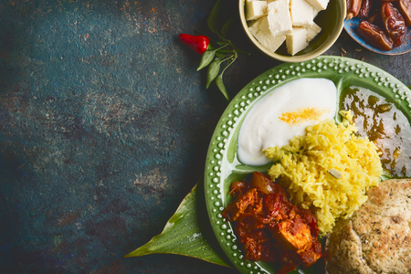 Various indian meal in bowl served on bamboo leaf  on dark rustic background, top view, place for text