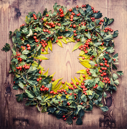 Autumn Wreath  of fall leaves and red berries  on wooden rustic background, top view
