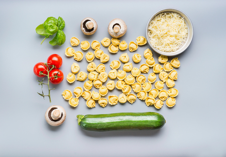 Flat lay of Raw tortellini pasta with ingredients for tasty vegetarian cooking on gray background , top view . Italian cuisine food concept