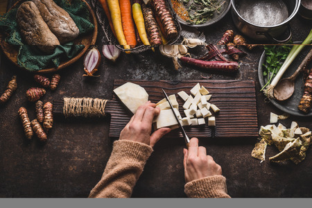 Female hands chopping celery on dark rustic kitchen table background with various vegetables and utensils. Root vegetables cooking preparation for tasty autumn dishes, top view. Healthy eating concept