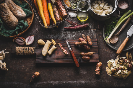 Jerusalem artichoke peeling preparation on rustic kitchen table with pot, diced vegetables, oil and ingredients, top view. Healthy and clean seasonal food cooking and eating concept