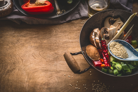 Wok pot with vegetarian asian cuisine ingredients for stir fry with chopped vegetables, spices, sesame seeds and lemongrass on rustic wooden background, top view. Chinese or Thai food cooking concept Stock Photo