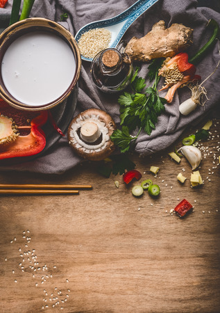 Vegetarian Asian cuisine ingredients with chopped vegetables, coconut milk, seeds, spices and chopsticks on rustic wooden background, top view. Chinese or Thai food cooking Stock Photo