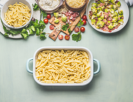 Cooking preparation of pasta casserole with romanesco cabbage and ham in creamy sauce ready for bake, on kitchen table background with ingredients, top view.  Italian cuisine Banco de Imagens - 90425832