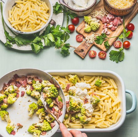 Woman female hands cooking pasta casserole with roasted romanesco cabbage and ham in creamy sauce on kitchen table background with ingredients, top view .  Italian cuisine
