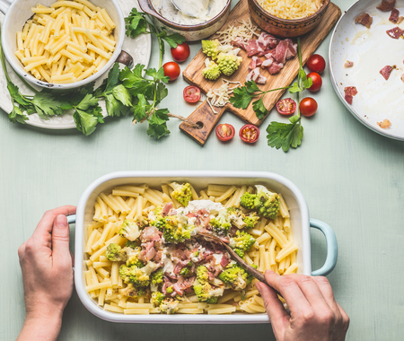 Woman female hands with spoon cooking pasta casserole with romanesco cabbage and ham in creamy sauce on kitchen table background with ingredients, top view. Italian cuisine