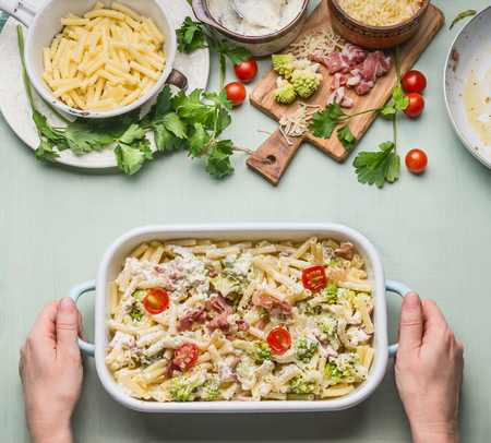 Woman female hands holding pasta casserole with romanesco cabbage and ham in creamy sauce, on kitchen table background with ingredients, top view, border.  Italian cuisine Imagens