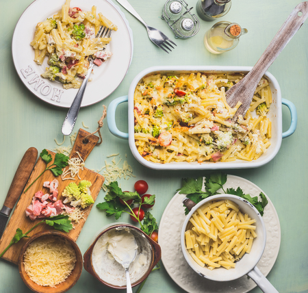 Pasta casserole with romanesco cabbage and ham in creamy sauce,  served in plate with cutlery on kitchen table with ingredients, top view. Italian cuisine