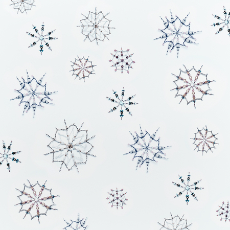 Christmas or winter concept. Pattern of various handmade snowflakes made from beads on blue sky background, top view Stock Photo
