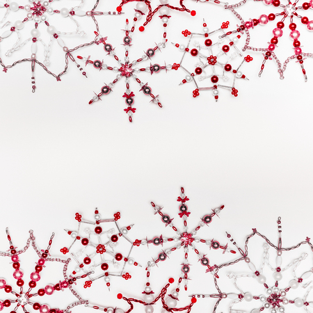 Christmas or winter concept. Frame of various handmade red snowflakes made from beads and bugle on white desk background, top view. Layout for greeting card and winter holidays