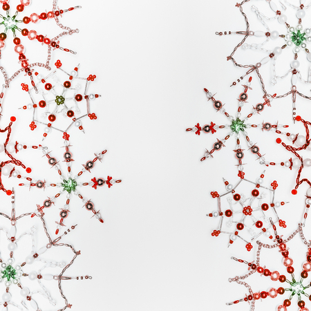 Christmas or winter concept. Frame of various handmade red green snowflakes made from beads and bugle on white desk background, top view. Layout for greeting card and winter holidays