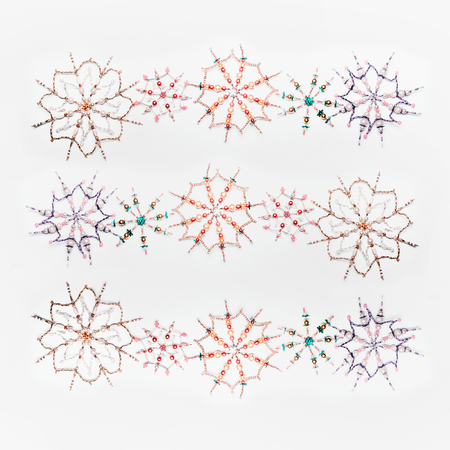 Christmas or winter concept. Pattern of various handmade snowflakes made from beads and bugle on white desk background, top view. Layout for greeting card and winter holidays