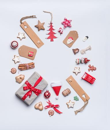Runde Weihnachtsrahmen-Planzusammensetzung für Grußkarte mit Kraftpapier, Tags und Geschenken, Feiertagsplätzchen, Schokolade, Lebkuchen und roter festlicher Dekoration auf weißem Hintergrund, Draufsicht. Standard-Bild