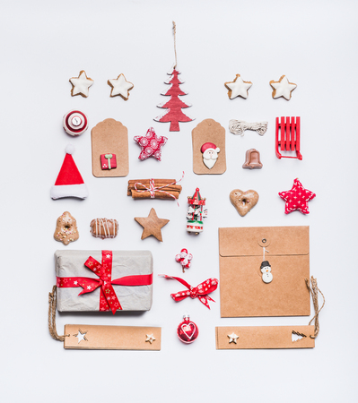 Christmas layout with craft paper wrapping gift boxes, tags, cookies, red holiday decoration, present, spices, Santa hat and red Christmas tree on white desk background, top view, flat lay.