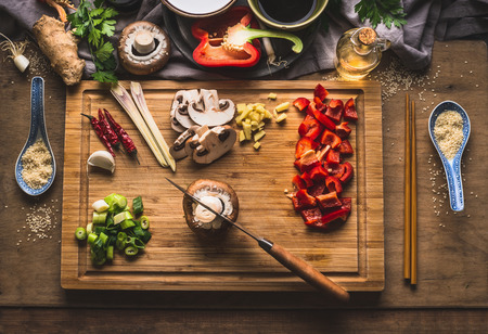 Copped vegetables ingredients for tasty vegetarian stir fry dishes on wooden cutting board with knife and chopsticks, top view. Asian cuisine. Healthy eating and food concept Stock Photo