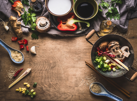 Vegetarian stir fry cooking preparation on wooden background with various vegetables, wok, coconut milk, seeds and kitchen utensils, top view, frame. Asian cuisine. Healthy eating and food concept