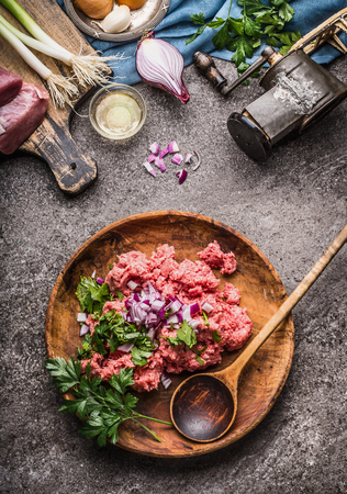 Raw minced meat stuffing in wooden bowl and spoon on gray stone background with meat grinder, and ingredients , top view, place for text. Cooking,recipes and eating concept