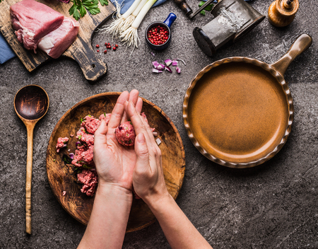 Female hands making meat balls on kitchen table background with  meat, force meat , meat grinder and spoon, top view. Cooking,recipes and eating concept