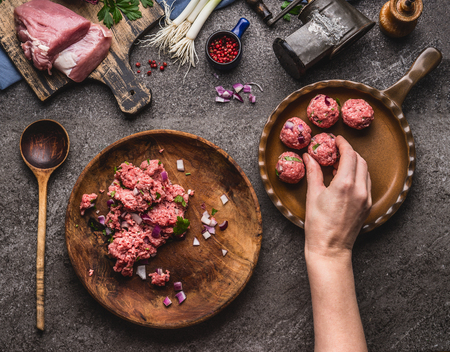 Meat balls making. Female hand puts meat ball in frying pan. Preparation on kitchen table with meat, force meat , meat grinder and spoon, top view. Cooking,recipes and eating concept