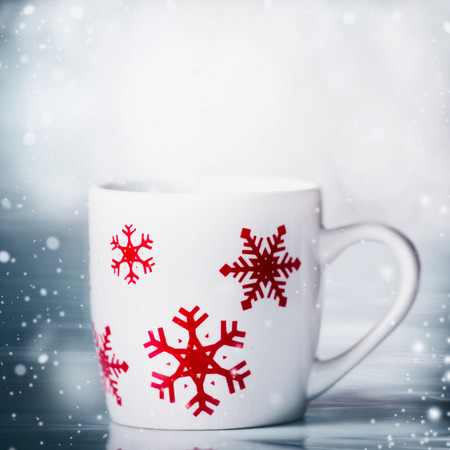 White mug with red snowflakes on blue snowfall background, front view. Happy winter holiday card layout