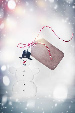 Happy snowman with tag mock up and ribbon at snowy winter day background. Winter holidays card Stock Photo