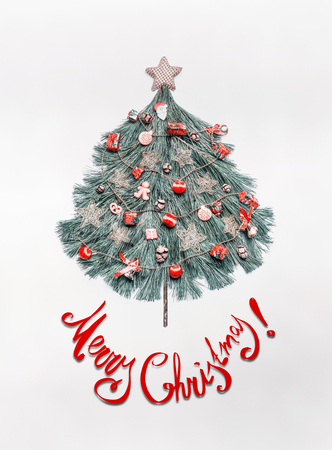 Merry Christmas card with lettering, tree made with fir branches, decorated with star and red festive decorations , holidays cookies, gingerbread man and Santa on white background, top view.